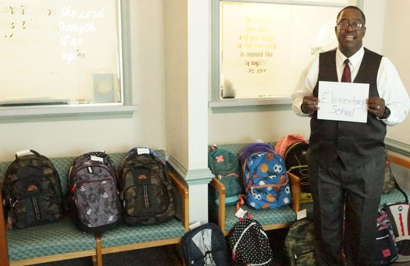 Rev. Hooker preparing back packs.